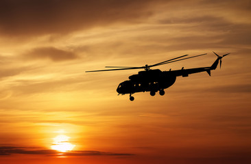 Picture of helicopter at sunset. Silhouette of helicopter