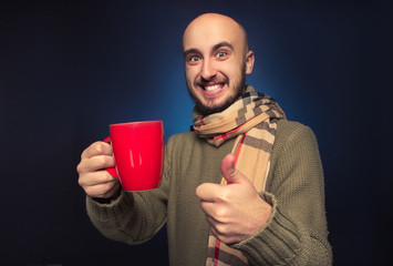 smiling man wearing a scarf and a cup in hand