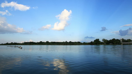 Lake with blue sky and clouds reflected in water.