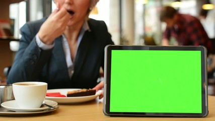 tablet green screen - woman eats cake and drinks coffee