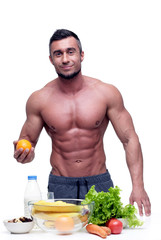 Smiling muscular man standing with vegeterian food