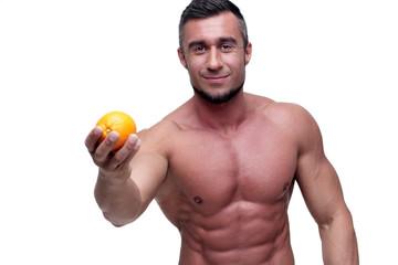 Happy muscular man holding orange over white background