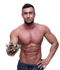 Smiling muscular man holding salad over white background