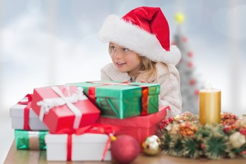 Composite image of cute little girl with gifts