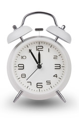 White alarm clock with hands at 5 minutes till 12
