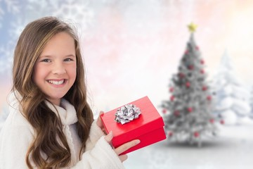 Composite image of girl holding gift