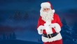 Composite image of happy santa holding paper and pen
