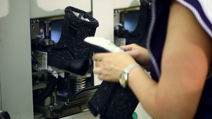 Working woman checks workpiece boots, close-up