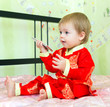 Baby with cell phone in festive costume sitting on the bed