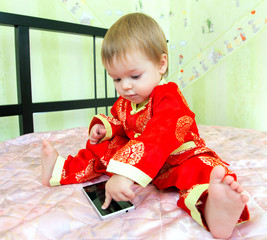 Little boy in holiday suit touches telephone screen
