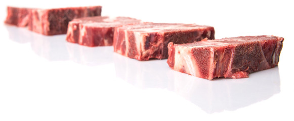 Chunk of cut frozen beef meat over white background