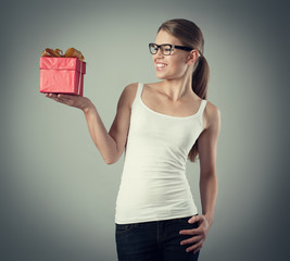 Joyful girl holding present box celebrating win or victory