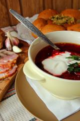 A plate of hot borscht with sour cream.