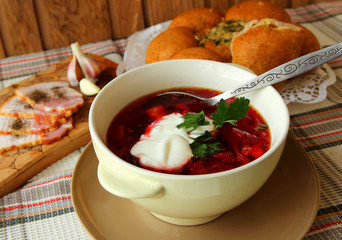 A plate of hot borscht with sour cream, bread and meat.