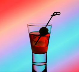 Short drink glass with red liquid and green olive