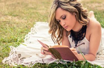 Romantic girl writing in a diary lying down outdoors