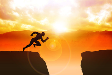 Silhouette of a male figure sprinting to jump the ravine