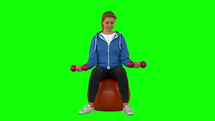 Fit blonde sitting on exercise ball lifting hand weights