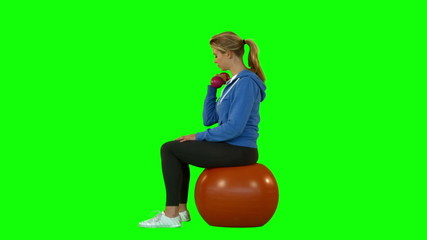Side view of fit woman with dumbbell sitting on exercise ball
