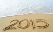 Year ,2015 hand written on the white sand in front of the sea