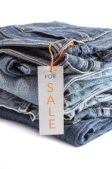 Pile of blue jeans with tag label.