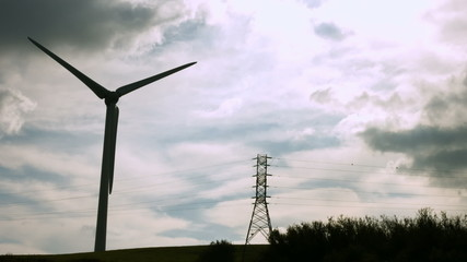 Windmill spinning against a grey sky