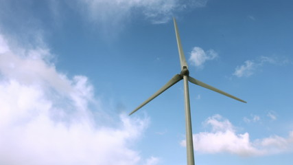 Wind energy spinning against a blue sky
