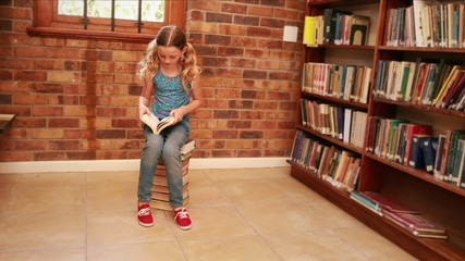 Cute pupil reading while sitting on pile of books