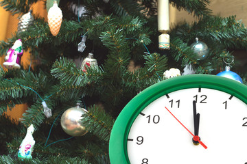 Clock showing twelve hours and dressed up Christmas tree