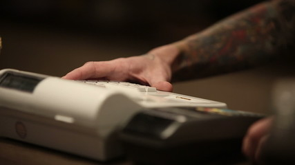 Seller man with tattoos on his hands and cash register
