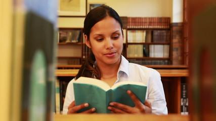 Pretty teacher taking book from shelf