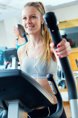 Young people with elliptic machine in the gym.