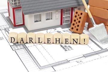 Bauplan mit Ziegelstein und Haus mit Darlehen