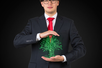 businessman holding tree