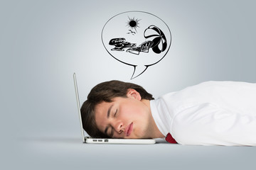 man sleeping on the laptop and dreaming about vacation