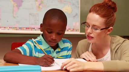 Pretty teacher helping pupil in classroom smiling at camera