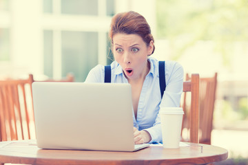 Shocked business woman using laptop looking at computer screen