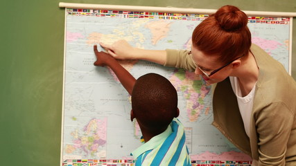 Cute pupil and teacher pointing to map