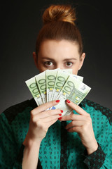Young woman covering her face with bunch of euro banknotes