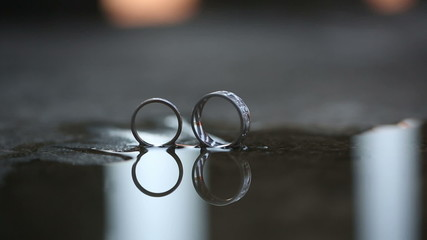 Reflection of beautiful wedding rings in a puddle