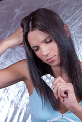 Young brunette woman with headache holding pills tablets