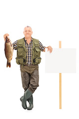 Mature fisherman holding a big fish next to a panel