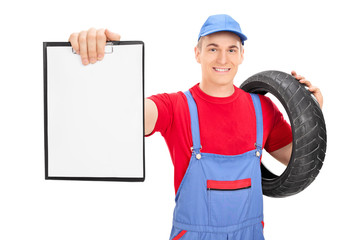 Male mechanic holding a tire and a clipboard