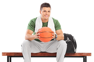 Young man with basketball sitting on a bench