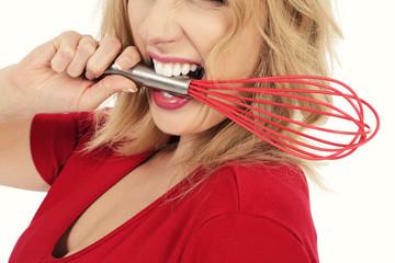 femme mordant fouet de cuisine