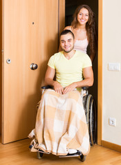 Woman with disabled husband at the door