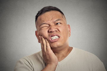 man touching face having bad pain, tooth ache grey background