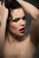 Hot sexy brunette woman in water studio, dark background