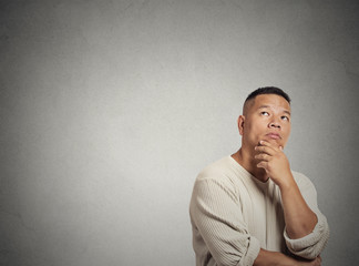 middle aged man thinking looking up on grey wall background