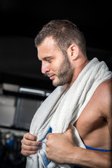 Man in gym with towel around neck